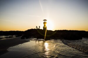 Silhouette of two people walking past lighthouse by the ocean at sunset.