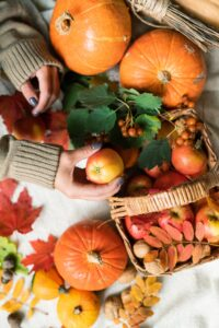 Woman taking apple from basket standing on table among ripe pumpkins and leaves