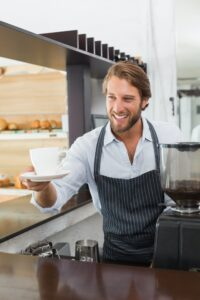 Handsome barista offering a cup of coffee at the coffee shop