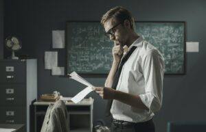 Young mathematician studying in his office and reading papers